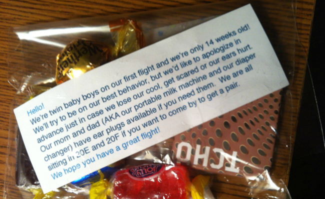 parents of twin babies give candy to passengers on airplane